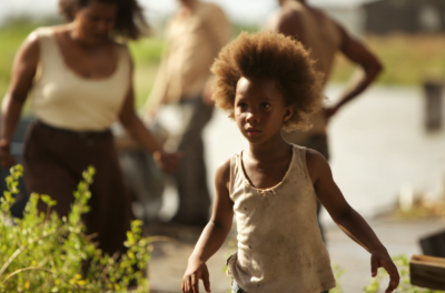 A young child runs away from a group of people who are out of focus in the background