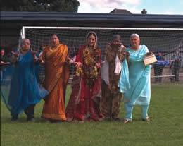 Still of five Indian women standing in front of a goal on a football field