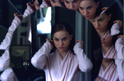 Multiple images of woman in dressing gown shown in mirror reflections.
