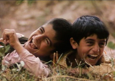 A close up of two boys lying on the grass laughing