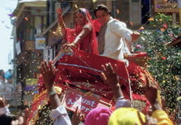 Still of a married couple waving to a crowd surrounded by confetti