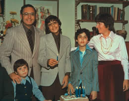A family photograph of a man, a woman and three boys dressed in suits