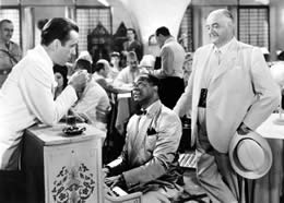 Still of people standing around a man playing piano in a restaurant