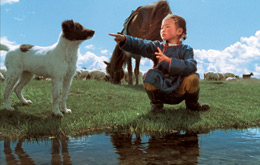 A child crouches, pointing past a dog. They are stood next to the waters edge.