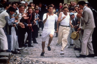 2 men in period clothing running, with a cheering crowd
