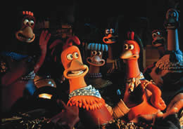 Still of smiling chickens gathered around a rooster