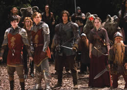 Still of people standing in armour in preparation for battle