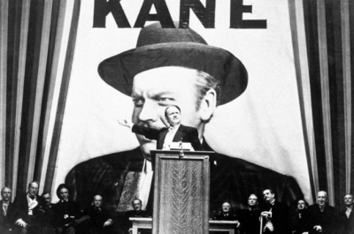 A man stands by a lectern with a row of men in suits behind him and a large poster of himself above his head