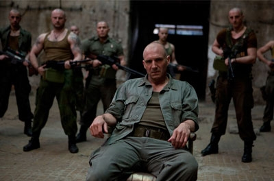 A man in military fatigues slouches in a chair, with aothe rmen holding guns in the background