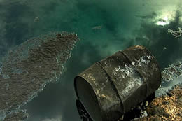 An oil drum lies next to oily water with oil spilling out