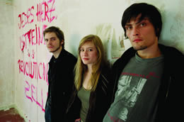 Still of three youths standing against a graffitied wall