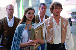 Still of a girl holding a large book with men standing around her
