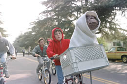 A boy in a red hoodie cycles with an alien in his bike basket.