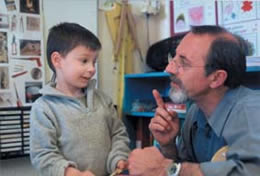 Still of a man kneeling to talk to a young boy
