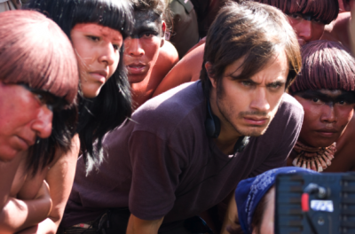 A man bends down to look at a camera amidst a crowd of people