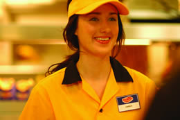 Still of a lady taking an order in a fast-food restaurant