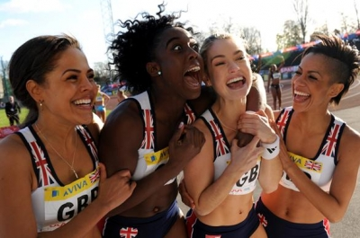 A group of young girls wearing athletics kit hug each other