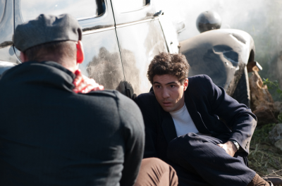 A man crouches down behind a car looking at another man who is also crouching with his back to the camera