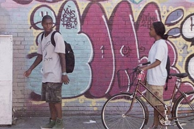 Two teenagers stand in front of some graffiti on an urban wall