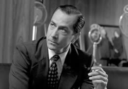 Still in black and white of a man in a suit holding a cigarette