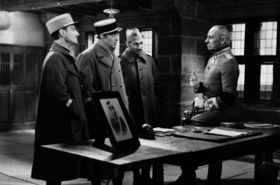 A man in a uniform sits on the edge of a desk while 3 other men in uniform face towards him