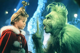 A hairy green creature talks to a young girl