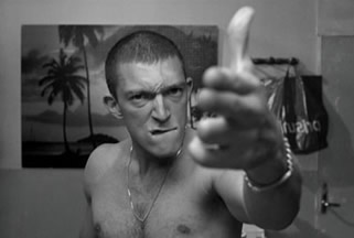 Black and white image of topless man making gun gesture with fingers, in bathroom mirror
