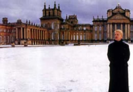 Still of a man standing outside a mansion in the snow