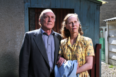 An elderly couple stand arm in arm outside of a house
