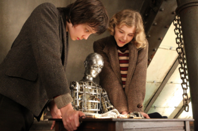 A boy and girl look over the shoulder of an automaton who is writing at a desk