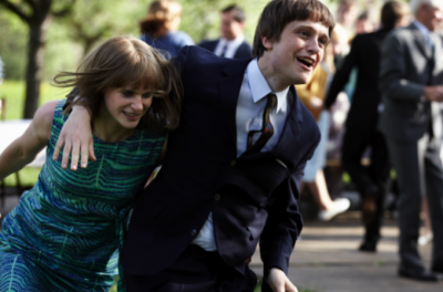 A young man puts his arm around a young woman as they run through a crowd