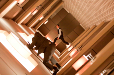 Two men float whilst fighting in a hotel corridor.