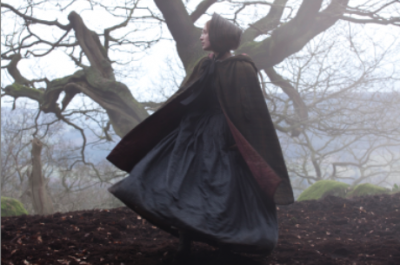A woman wearing a cloak and hat runs through the woods