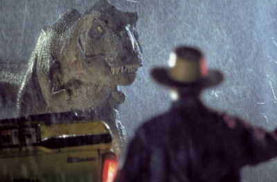A man holding a flare faces away from the camera as a tyrannosaurs heads towards him