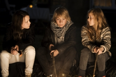 Two teenage girls sit either side of a teenage boy