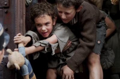 A young child cries and holds onto a steel door as a woman holds her back