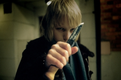 Boy holding up a knife in a threatening manner