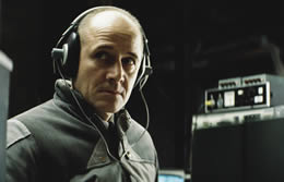 A man wearing headphones sits in a dark room looking worried