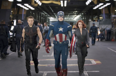 A man wearing a uniform and shield in the pattern of the American flag walks through a hanger with a man and woman in black walking on either side