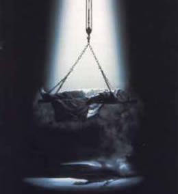 Still of a body lying on a board hanging from a chain