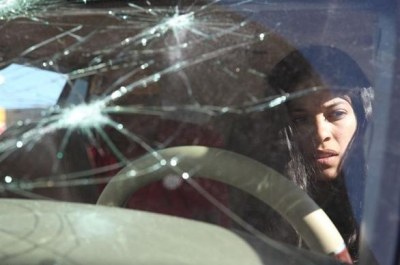 A young woman sits at a steering wheel behind a broken windscreen