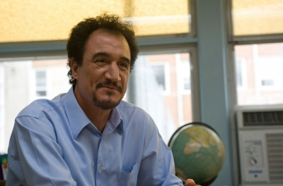 A mid shot of a man smiling with a window and a globe in the background