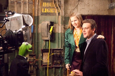 Wide shot of a muppet talking to 2 humans, backstage at a theatre