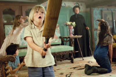 A young boy in the foreground holds a cricket bat up in astonishment.  There are some young girls behind him and a woman in black standing in the background.