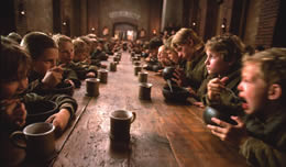 Rows of boys sit at a long table eating from small bowls