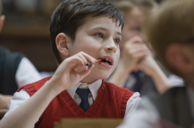 A close up of a young boy sitting at a desk in a classroom, chewing his pen
