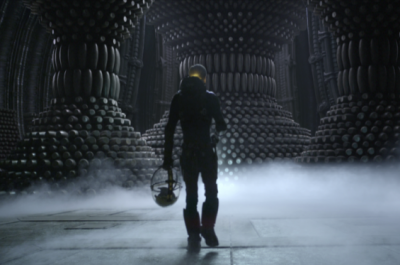 A man in a spacesuit walks through a cavernous chamber as smoke rolls across the floor
