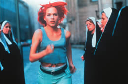 A woman with red hair runs through a group of nuns