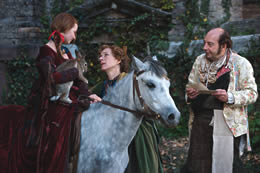 A woman talks to a girl on a horse holding a rabbit and a man stands watching