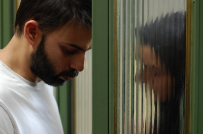 A man leans his head against the door and a woman leans against a pane of glass on the other side